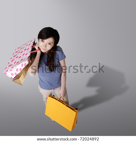 Cheerful shopping woman holding bags in studio background of gray.