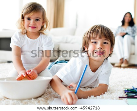 Cheerful siblings eating chips and drawing lying on the floor