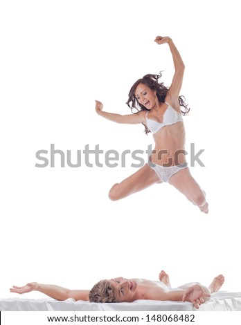 Cheerful slim woman jumping into bed with sexy guy