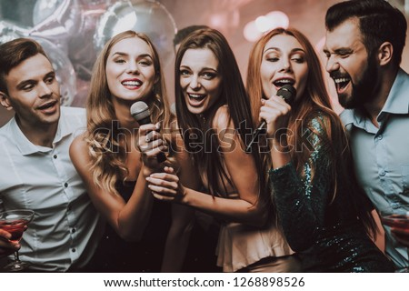 Cheerful. Smile. Smiling Girl. Singing Songs. Beautiful Girls. Friends at Karaoke Club. Karaoke Club. Celebration. Waiting Men. Young People. Party Maker. Girls Sing. Trendy Nightclub. Have Fun.