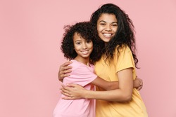 Cheerful smiling african american young woman and little kid girl sisters wearing casual t-shirts hugging looking camera isolated on pastel pink color background studio portrait. Family day concept