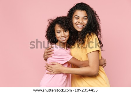 Cheerful smiling african american young woman and little kid girl sisters wearing casual t-shirts hugging looking camera isolated on pastel pink color background studio portrait. Family day concept Foto stock ©
