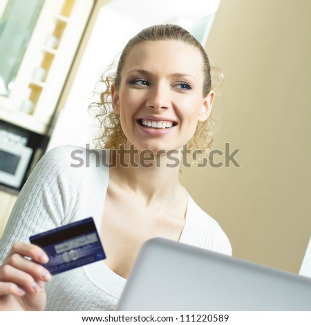 Cheerful smiling blond woman paying by plastic card with laptop, indoors