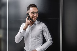 Cheerful smiling businessman standing indoors and using smart phone.