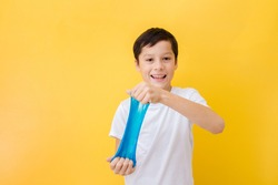 cheerful smiling caucasian boy with dark hair in white t shirt on yellow background stretches blue slime in his hands.