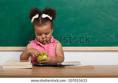 Cheerful smiling child (girl) at the blackboard. School concept