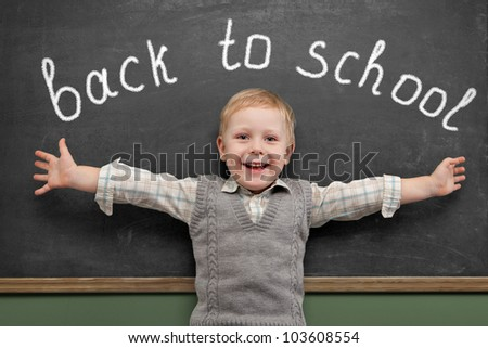 Cheerful smiling child  stands at the blackboard. Looking at camera. School concept