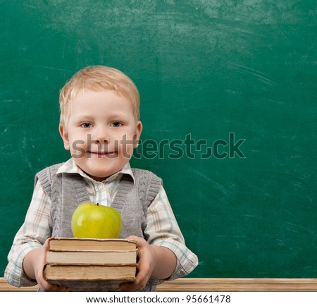 Cheerful smiling child with a book and apples stands at the blackboard . Looking at camera. School concept