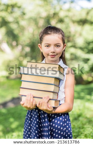 Cheerful smiling children girl hold chalkboard at the park . School learning concept at the park . School learning concept
