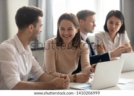 Cheerful smiling colleagues business team having fun talking at work break, happy millennial coworkers laughing at funny joke chatting working together sitting at shared office desk with laptops
