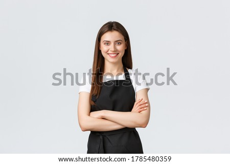 Cheerful smiling female barista in black apron cross arms chest, looking ready and confident. Young girl employee open coffee shop, greeting customers. Saleswoman running store