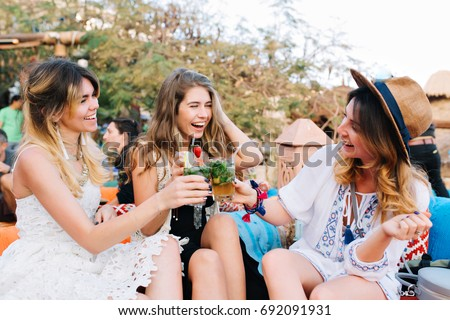 Cheerful smiling girls drink for the long-awaited meeting, while spending time in outdoor cafe in summer day. Attractive young women having fun outside, holding glasses of juice and cocktail