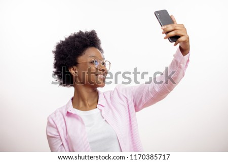 cheerful, smiling, gorgeous, charming woman taking picture of herself. female likes selfie, girl shotting her hairstyle aftre spa salon. close up side view shot. studio shot. #1170385717