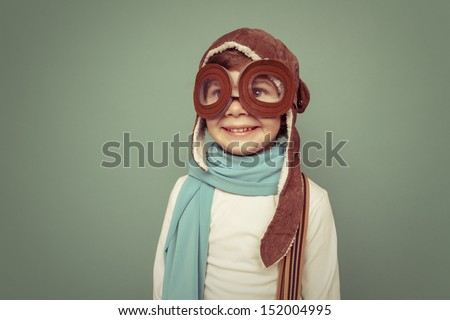 Cheerful smiling kid (boy)l in helmet on a green background. Vintage pilot (aviator) concept