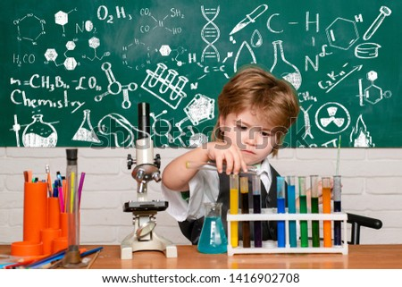 Cheerful smiling little boy having fun against blue wall. First grade. Science and education concept. My chemistry experiment. Experiment. What is taught in chemistry