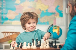Cheerful smiling little boy sitting at the table and evincing gladness while playing chess. Clever concentrated and thinking child while playing chess. Education and people concept
