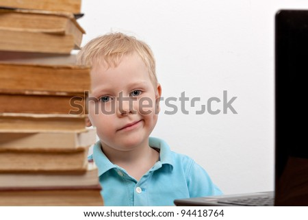 Cheerful smiling  little boy sitting at the table. Looking at camera. School concept - stock photo