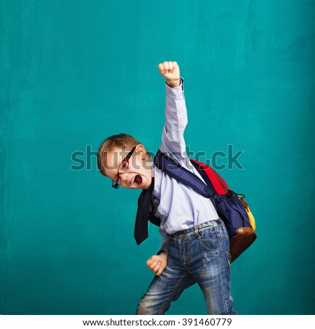 Cheerful smiling little boy with big backpack jumping and having fun against blue wall. Looking at camera. School concept. Back to School #391460779