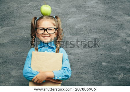 Cheerful smiling little kid (girl) against chalkboard. Looking at camera. School concept