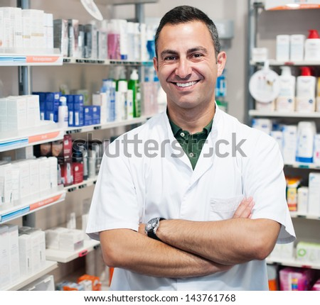 cheerful smiling pharmacist chemist man standing in pharmacy drugstore