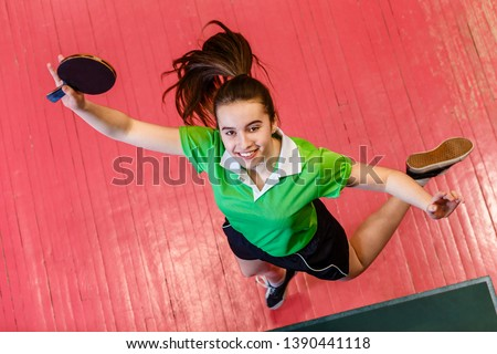 cheerful smiling teen girl jumping. Teen girl holding a table tennis racket, top view