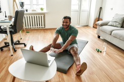 Cheerful stretching. Male fitness instructor showing exercises while streaming, broadcasting video lesson on training at home using laptop. Sport, online gym concept. Horizontal shot