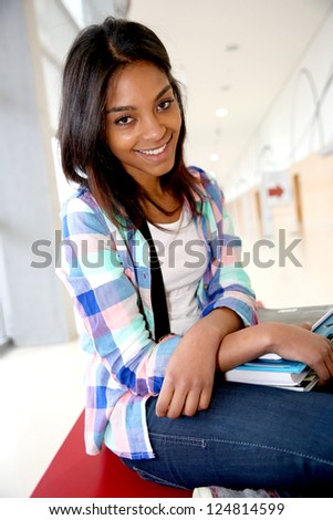 Cheerful student girl sitting on school bench