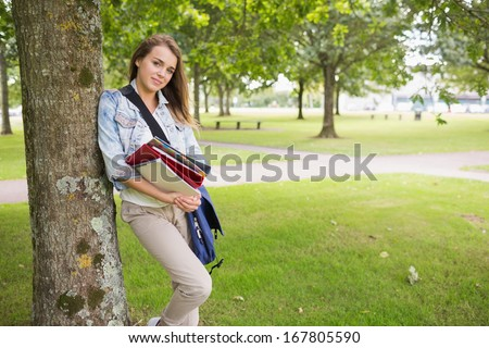 Cheerful student leaning on tree holding her books on college campus