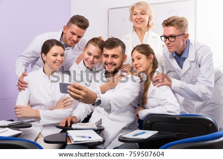 Cheerful students of medical faculty with female teacher making selfie indoors #759507604