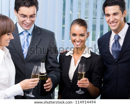 Cheerful successful business team celebrating with champagne at office