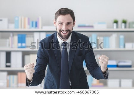 Cheerful successful businessman smiling in his office with raised fists, winning and enthusiasm concept #468867005