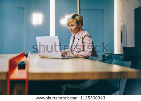 Cheerful successful businesswoman 50 years old watching interesting webinar online via wireless 4G internet on modern laptop device sitting in coworking space.Positive mature woman working at netbook