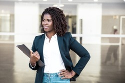 Cheerful successful manager with documents posing outside. Young black business woman standing at glass wall, holding folder, looking away, smiling. Successful professional concept