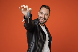Cheerful successful young bearded man 20s wearing basic white t-shirt, black leather jacket standing hold in hands car keys looking camera isolated on bright orange colour background studio portrait