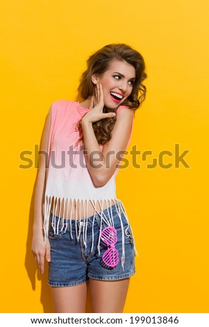 Cheerful summer girl. Smiling beautiful young woman looking away. Three quarter length studio shot on yellow background.