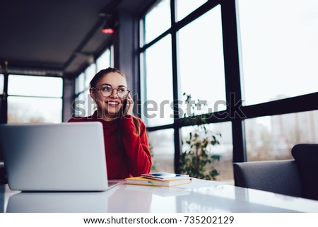 Cheerful talented female copywriter in eyeglasses having mobile conversation with friends in funny atmosphere via smartphone application.Smiling cute hipster girl talking on telephone indoors