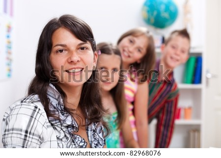 Cheerful teacher in front, several students in back