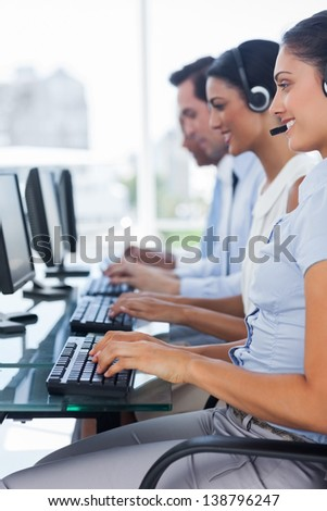 Cheerful team of call centre employees working on computers