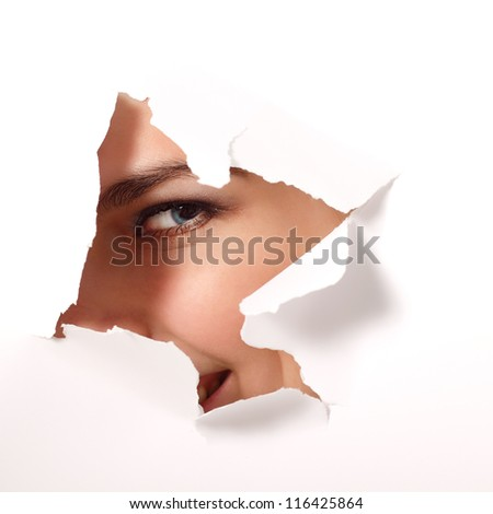 cheerful teen girl peeping surprised through hole of white paper