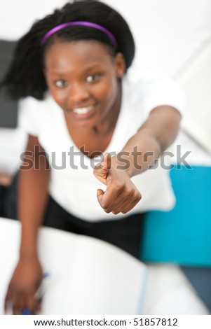 Cheerful teen girl with a thumb up studying sitting on her bed
