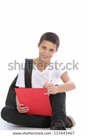 Cheerful teenage boy sitting curled up on the floor with a clipboard writing notes for his studies at college
