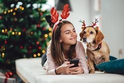 Cheerful teenage girl and her dog wearing deer antlers