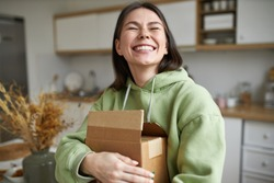 Cheerful teenage girl expressing positive emotions receiving unexpected birthday gift holding parcel and smiling with pleasure. Dark haired young woman posing with cardboard box with new cosmetics