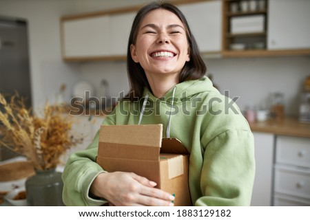 Cheerful teenage girl expressing positive emotions receiving unexpected birthday gift holding parcel and smiling with pleasure. Dark haired young woman posing with cardboard box with new cosmetics Photo stock ©