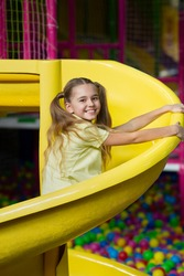 Cheerful teenage girl riding playground slide, having fun at indoor amusement park. Adorable adolescent kid spending weekend at children entertainment centre. Weekend pastimes concept
