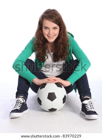 Cheerful teenage girl soccer player sitting on floor relaxing wearing green hoodie and blue jeans, holding football. - stock photo