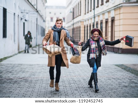 Cheerful teenager couple with paper bags walking down the street in winter.