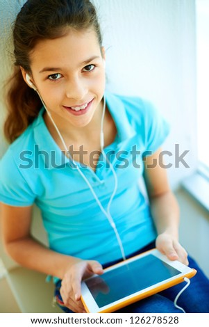 Cheerful teenager with a tablet computer listening to the music - stock photo