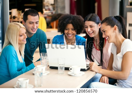 cheerful teenagers with laptop, internet cafe