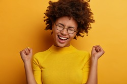Cheerful triumphing woman achieves victory, raises clenched fists with triumph, rejoices winning prize, dressed casually, keeps eyes closed, isolated over yellow background. Celebration concept